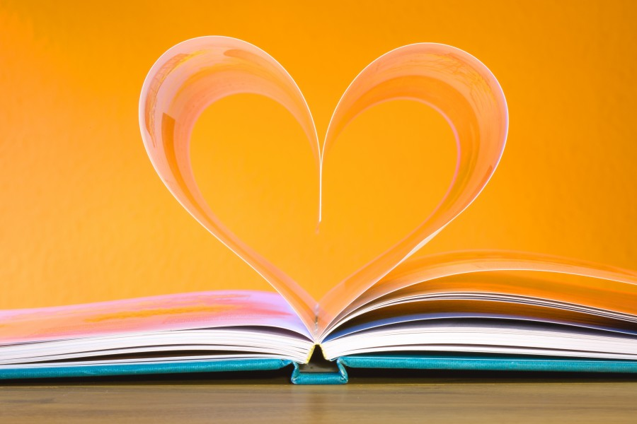 colourful book open with two inner pages forming heart shape