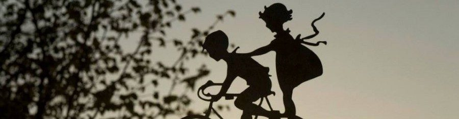 silhouette of young boy on bike with young girl standing on his back wheel
