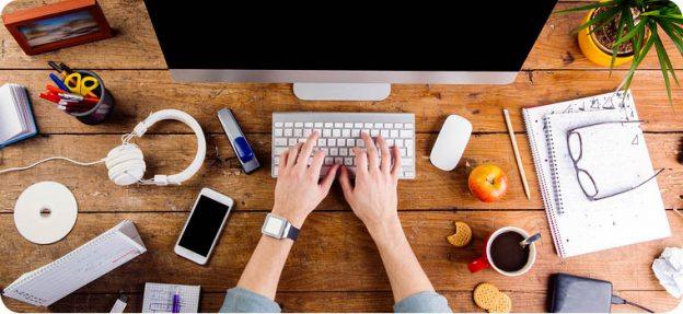 hands on keyboard surrounded by writing tools