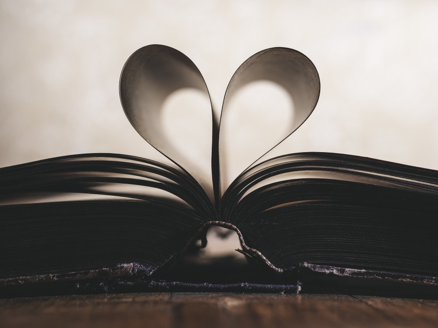 black and white book open with inner pages forming heart shape