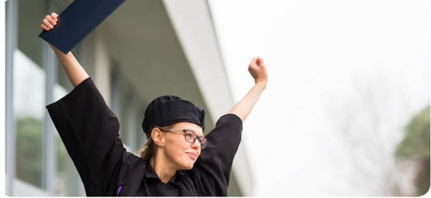 woman graduate celebrating with arms in the air